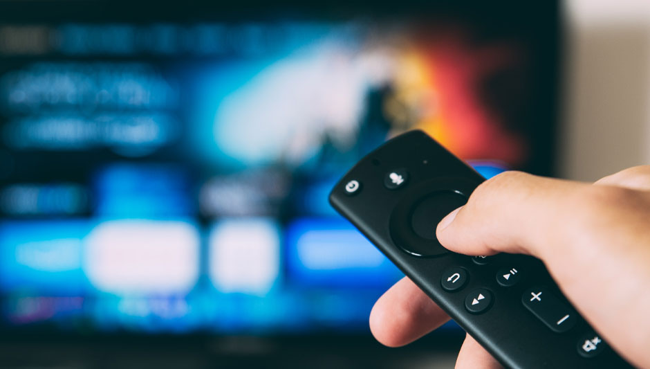 hand on remote control pointed at a tv
