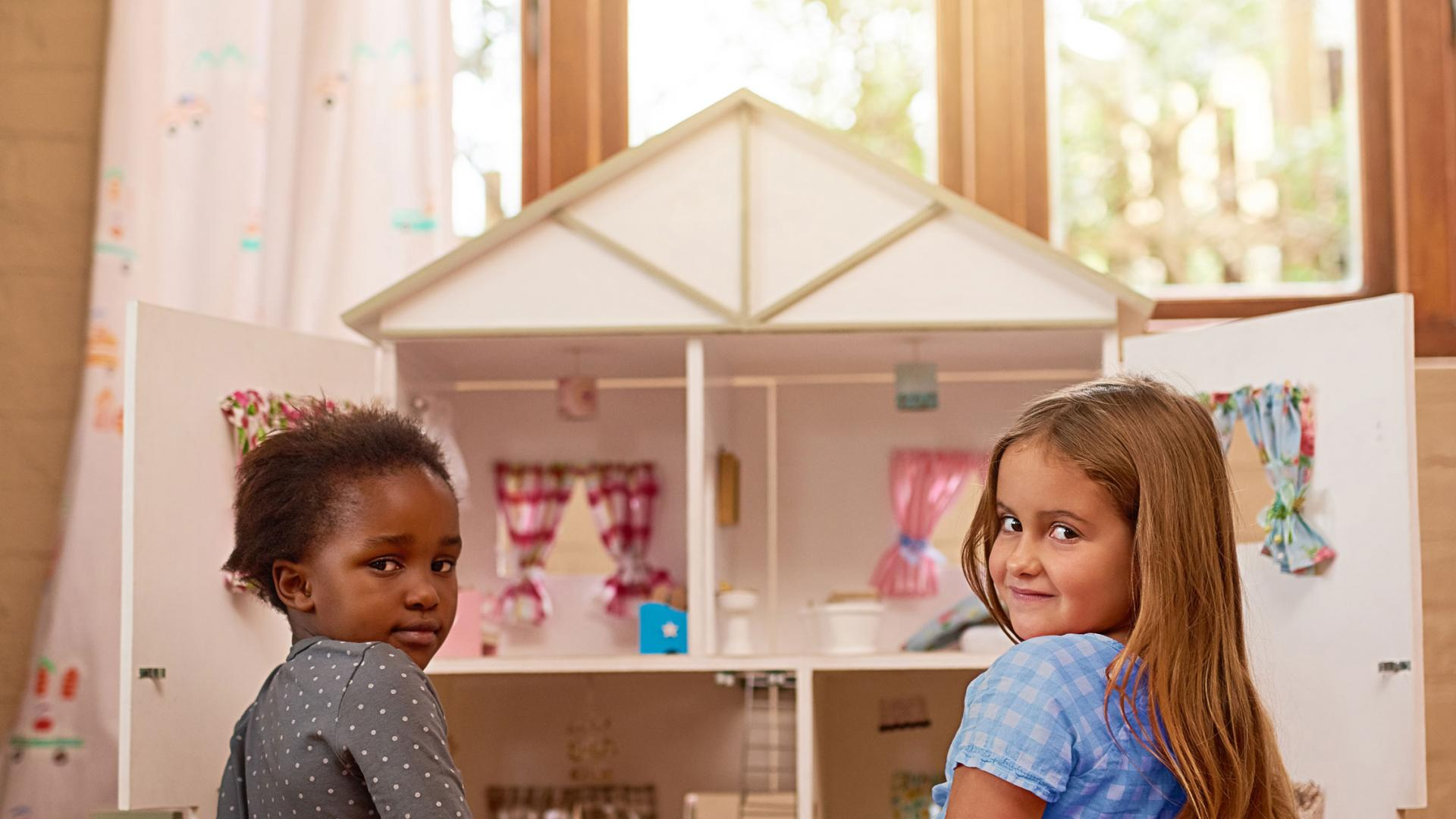 two girls sitting in front of an open dollhouse in front of a window