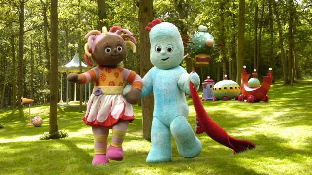 a female creature in a colourful outfit walking through the forest with a blue creature