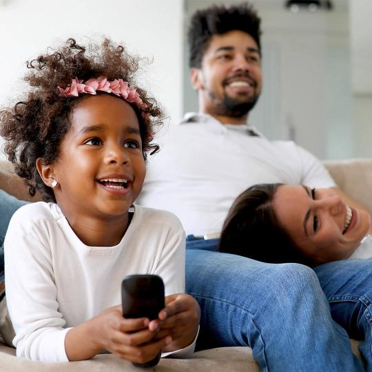 A family sitting on the couch watching TV and a young girl holding the remote.