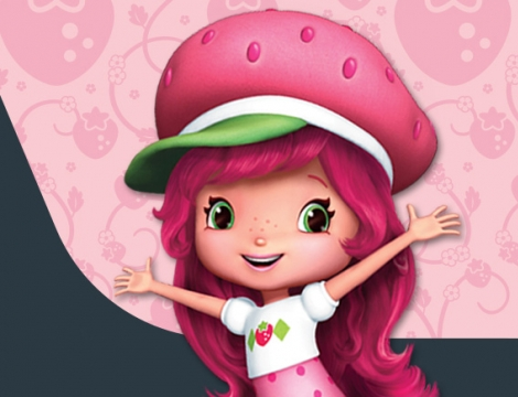 A close-up of a smiling girl with pink hair and a pink hat, shaped like a strawberry. Her arms are open wide and she is standing in front of a pink background.